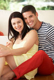 Par som hemma kopplar av på sofaen Royaltyfria Foton