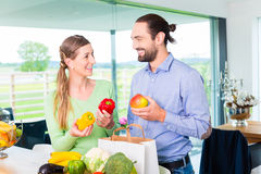 Par som hemma packar upp livsmedelsbutikshoppingpåsen Royaltyfria Bilder