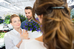 Par som hjälps av blomsterhandlaren In Buying Flower royaltyfri fotografi