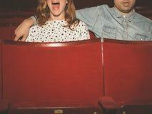 Par som håller ögonen på en film i en filmbiograf Arkivfoton