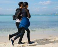 Par som joggar längs stranden fotografering för bildbyråer