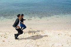 Par som joggar längs stranden arkivbilder
