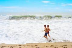 Par som joggar på thstranden Arkivfoto