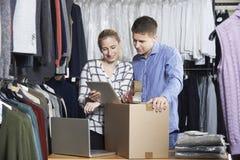 Par som kör online-gods för emballage för klädlager för utskick royaltyfri foto