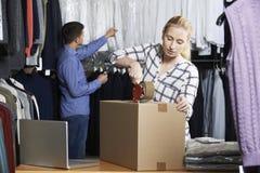 Par som kör online-gods för emballage för klädlager för utskick arkivbilder