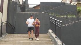 Par som kör på trappa i morgonen som joggar i stadsområde med starecases lager videofilmer