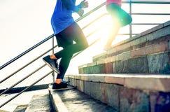 Par som kör på trappa på solnedgången - vänner som gör en genomkörareperiod som övar för att få på den utomhus- trappuppgången arkivbilder