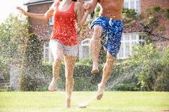 Par som kör till och med den trädgårds- sprinkleren Royaltyfri Foto