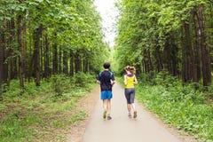par som kör utomhus Kvinna- och manlöpare som tillsammans joggar utvändig oavkortad kropplängd Royaltyfri Fotografi