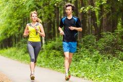 par som kör utomhus Kvinna- och manlöpare som tillsammans joggar utvändig oavkortad kropplängd Royaltyfri Bild