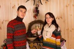 Par som kastar exponeringsglas av vin inom huset Royaltyfria Foton