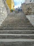 Par som klättrar den forntida stenen lantliga Grey Staircase och den gamla lantliga texturerade väggen som symboliserar utmaning  Royaltyfria Foton