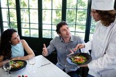 Par som klagar om maten till kocken fotografering för bildbyråer
