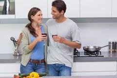 Par som klirrar deras exponeringsglas av rött vin Royaltyfri Foto