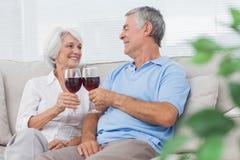 Par som klirrar deras exponeringsglas av rött vin Royaltyfria Bilder
