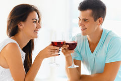 Par som klirrar deras exponeringsglas av rött vin Fotografering för Bildbyråer