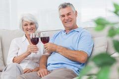 Par som klirrar deras rött vinexponeringsglas Arkivfoto