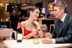 Par som klirrar exponeringsglas med rött vin Arkivbilder