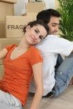 Par som kopplar av efter moving hus Arkivbild