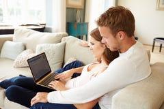 Par som kopplar av genom att använda bärbar datordatoren för internetbankrörelsen arkivbild