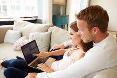 Par som kopplar av genom att använda bärbar datordatoren för internetbankrörelsen arkivbilder