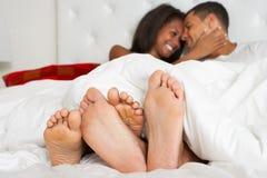 Par som kopplar av i bärande pyjamas för säng arkivfoton