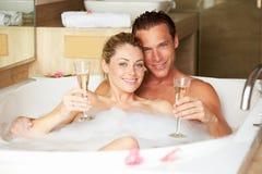 Par som kopplar av i badet som dricker Champagne Together Arkivfoto