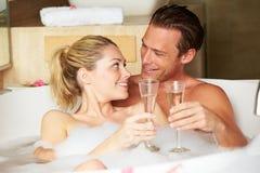 Par som kopplar av i badet som dricker Champagne Together Arkivbild