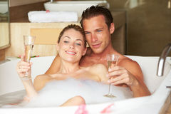 Par som kopplar av i badet som dricker Champagne Together Royaltyfria Bilder