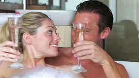 Par som kopplar av i badet som dricker Champagne Together stock video