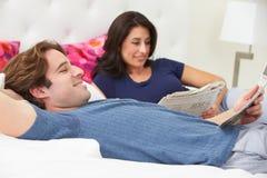 Par som kopplar av i bärande pyjamas för säng och läs- tidning Royaltyfria Bilder