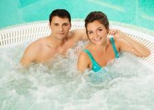 Par som kopplar av i en bubbelpool Royaltyfria Bilder