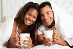 Par som kopplar av i säng med den varma drinken Arkivfoton