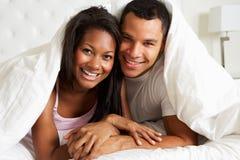 Par som kopplar av i sängnederlag under duntäcket Fotografering för Bildbyråer