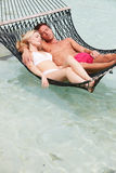Par som kopplar av i strandhängmatta royaltyfria foton