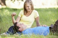 Par som kopplar av i Sunny Summer Field Royaltyfria Bilder