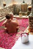 Par som kopplar av i täckt pöl för blomma kronblad på Spa Royaltyfri Foto