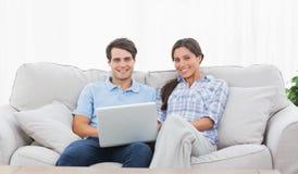 Par som kopplar av med en bärbar dator Royaltyfri Foto