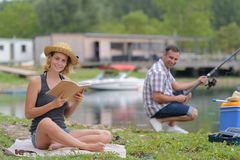 Par som kopplar av, medan fiska på sjön Arkivfoton