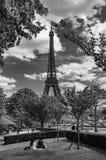 Par som kopplar av nära Eiffeltorn i Paris arkivfoton