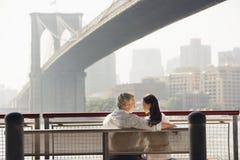 Par som kopplar av på bänk under den Brooklyn bron Fotografering för Bildbyråer