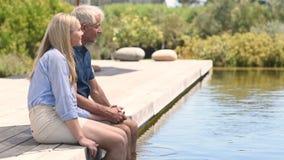 Par som kopplar av på poolsiden stock video