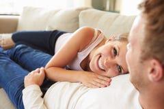 Par som kopplar av på Sofa At Home Together royaltyfri bild