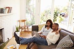 Par som kopplar av på Sofa At Home Using Laptop royaltyfri fotografi