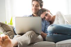 Par som kopplar av på Sofa With Laptop Arkivfoton