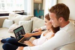 Par som kopplar av på Sofa Using Laptop Computer Together arkivbilder