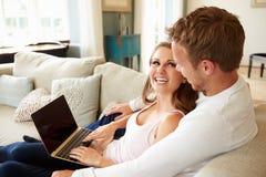 Par som kopplar av på Sofa Using Laptop Computer Together royaltyfri fotografi