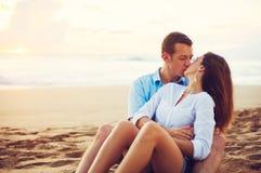 Par som kopplar av på stranden som kysser och håller ögonen på solnedgången Royaltyfri Fotografi