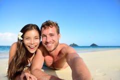 Par som kopplar av på stranden som tar selfiebilden Arkivbilder