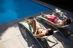 Par som kopplar av på vardagsrumstol på poolsiden Royaltyfria Bilder